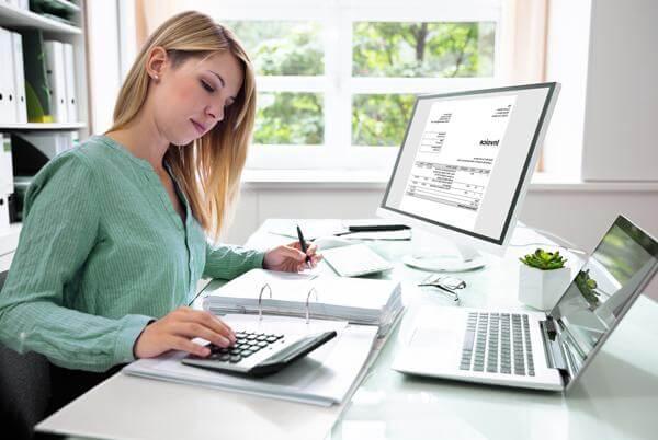kobieta wypełniająca dokumenty zpomocą kalkulatora